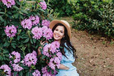 Beautiful young woman with long brunette hair in straw hat posing near flowers Rhododendron in a garden