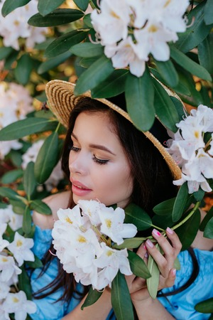 Close up romantic portrait of beautiful elegant woman in straw hat in blossom spring trees.