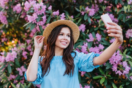 Beautiful smiling girl in summer outfit making selfie. Outdoor photo of romantic young woman in straw hat having fun in garden.