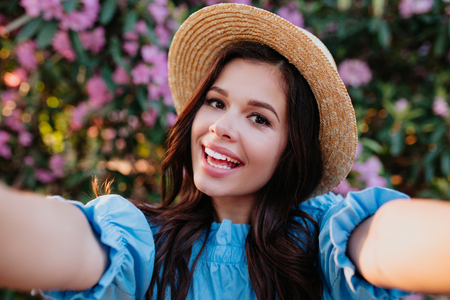 romantic young smiling woman in straw hat making selfie on flower background Reklamní fotografie