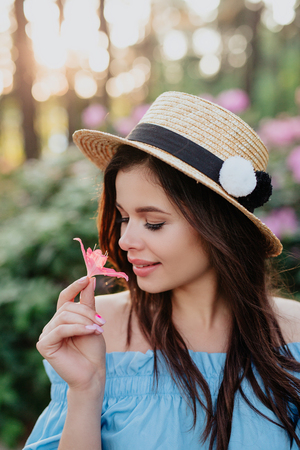 Close up portrait of lovely young romantic woman with flower in hand posing on sunset. Wearing straw hat. Soft colors.