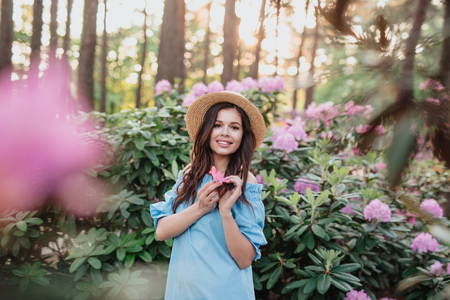 Beautiful girl in blue vintage dress and straw hat standing near pink flowers. Pretty tenderness model looking at camera