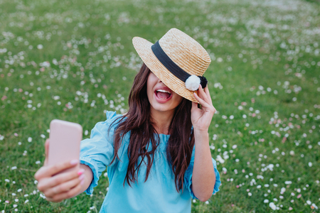 Close up of laughing brunette woman in straw hat sitting on grass in park and making selfie