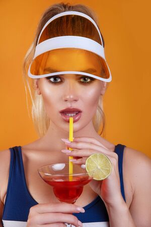 Sexy blond woman in swimsuit and trendy plastic visor holding glass of fresh drink on yellow background