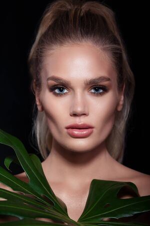 Beautiful woman face with fresh professional makeup in green leaves. Natural Beauty.