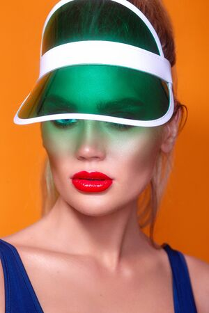 close up portrait of a beautiful young woman wearing sun visor. Fashion beauty and make up cosmetics concept