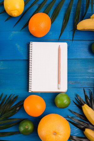 Group of exotic tropical fruits and palm leaves and notepad on blue wooden table Reklamní fotografie