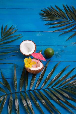 Coconuts, lime and palm leaves on blue wooden background. Flat lay, space for text