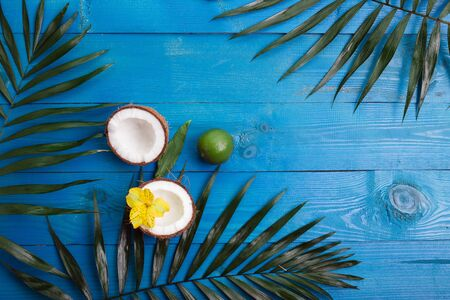 Various fruits, green leaves and flowers on blue wooden table. Tropical summer background with a space for a text,