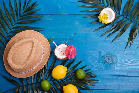 Tropical summer background with hat, palm leaves, lemons, lime, coconuts on blue wooden table