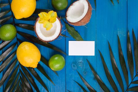 lemon, lime, coconut and palm leaves and business card on blue wooden background. Reklamní fotografie
