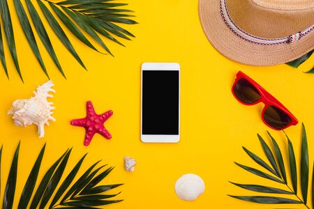 Hat, tropical palm leaves, sunglasses, sea shells and smartphone on yellow background. Flat lay