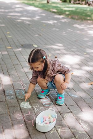 Cute toddler girl sitting and drawing shapes on asphalt in park. Child holding chalk.