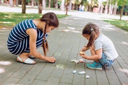Two cute little girls sitting and drawing with chalk on asphalt in park in summer day