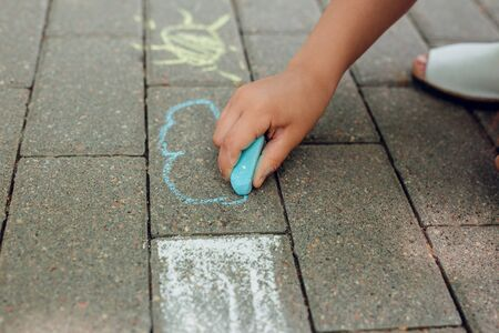 Childrens hand draws with chalk on the pavement in park.