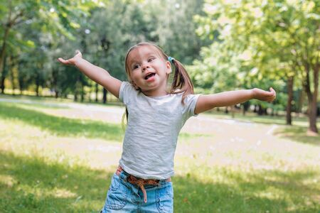 Happy little child in summer park. Young girl relax outdoors. Freedom concept
