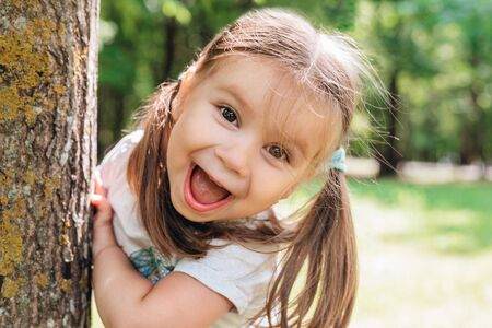 Close-up portrait of an excited little girl laughing in summer park