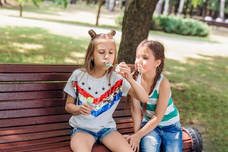Two cute little girls blowing soap bubbles in summer park.