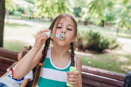 Cute little girl blowing soap bubbles in summer park.