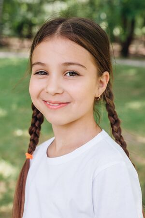 Portrait of adorable smiling little girl child with pigtails in white t-shirt outdoor in summer day