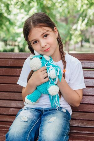 Portrait of adorable smiling little girl child with blue unicorn toy outdoor Reklamní fotografie
