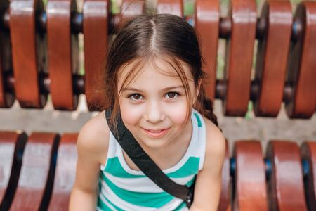 Cute little girl with pigtails sitting on the wooden bench in park Reklamní fotografie