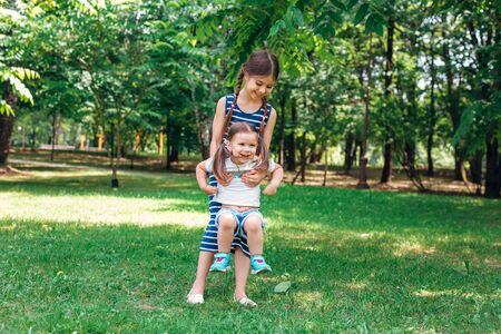 Two cute little sisters playing in park in sunny summer day Reklamní fotografie