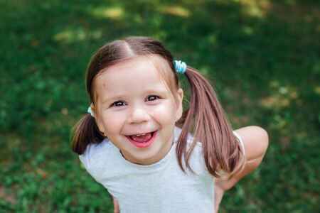 Portrait of funny beautiful little girl in the summer on the blur green background