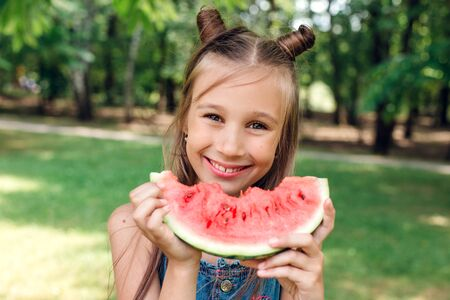 funny little girl eating watermelon and smiling in park in summertime