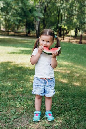 cute little girl eating watermelon in park in summertime Reklamní fotografie