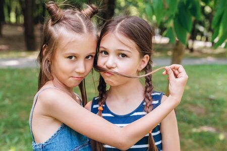 Two little girls having fun in park in sunny summer day