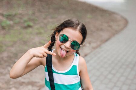 Fashion kid. Stylish little girl child in sunglasses having fun in city