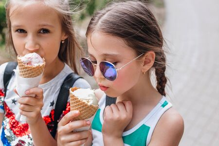 Portrait of 8-9 years old kid girls eating tasty ice cream in park Reklamní fotografie