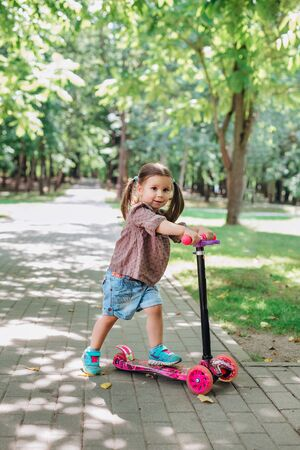 Little child girl learning to ride a scooter in a city park on sunny summer day.