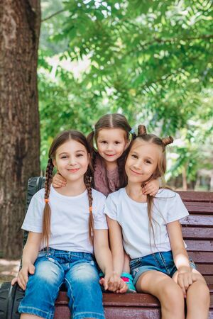 Outdoor portrait of three embracing cute little girls in summer park