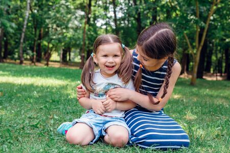 Two cute little sisters having fun in park in sunny summer day