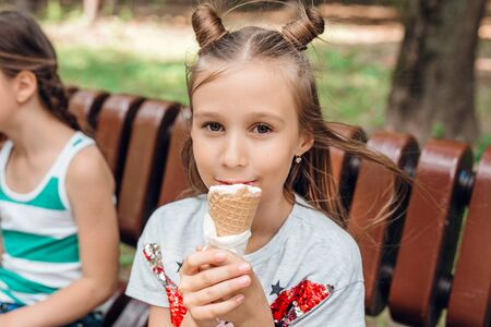 Pretty little girl sitting on bench and eating an ice cream outdoors Reklamní fotografie