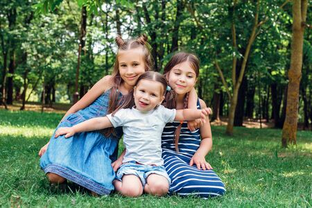 Three cute little sisters playing in park in summer day Reklamní fotografie