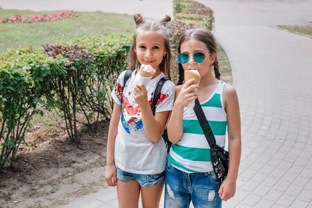 Portrait of 8-9 years old kid girls eating tasty ice cream in summer park