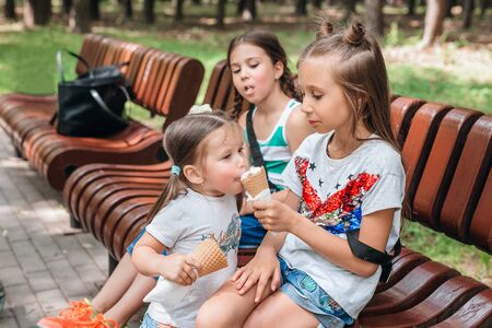 Cute girl share ice cream with her little sister in park