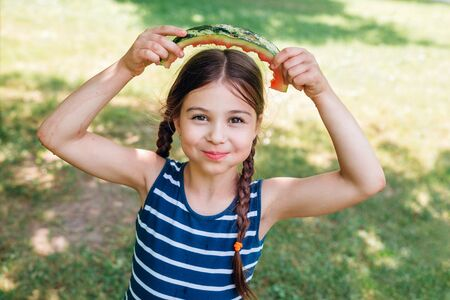 funny little girl eating watermelon in park in summer sunny day