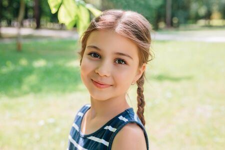 Portrait of adorable smiling little girl child with pigtails outdoor in summer day Reklamní fotografie