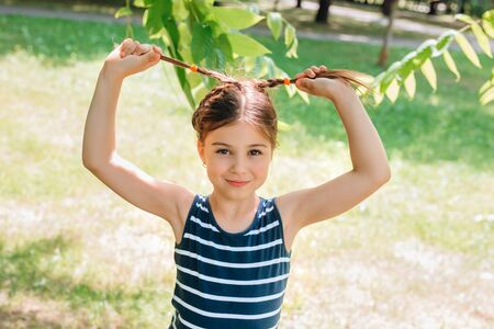 little girl child with pigtails having fun in park in summer day