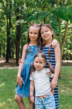 Portrait of three happy kids in sunny day in park. Friendship. Family time Reklamní fotografie