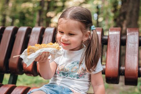 Close-up of adorable 4 years old girl child eating sweet corn in summer park Reklamní fotografie