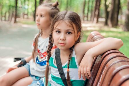 Two cute little girls sitting on the wooden bench in summer park