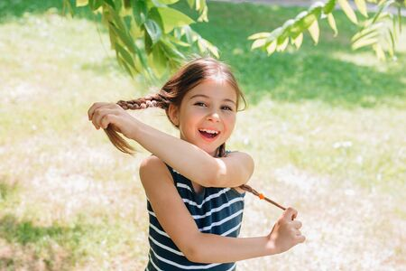 little girl child with pigtails having fun in park in summer day Reklamní fotografie - 126968980
