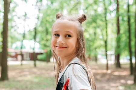 Portrait of funny beautiful little girl with cute horns hairstyle in the summer Reklamní fotografie