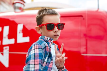 Stylish little boy in red sunglasses shows peace signoutdoor Reklamní fotografie