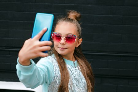 Pretty little girl in sunglasses making a selfie using a smart phone and smiling outdoor